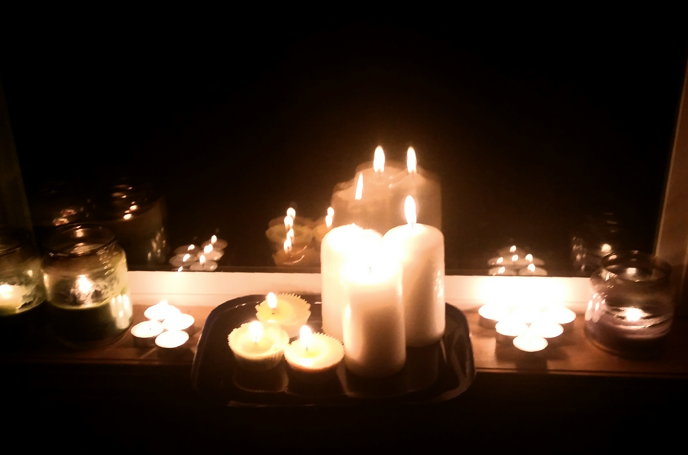 candles set up on a windowsill provide a golden light contrasted with the surrounding darkness